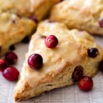 three cranberry orange scones on white plate