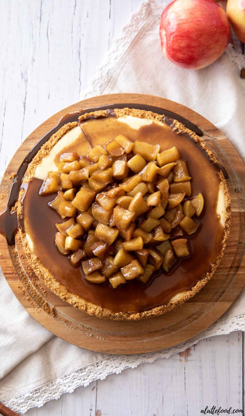 whole apple cheesecake with cramel sauce on a wooden cake stand