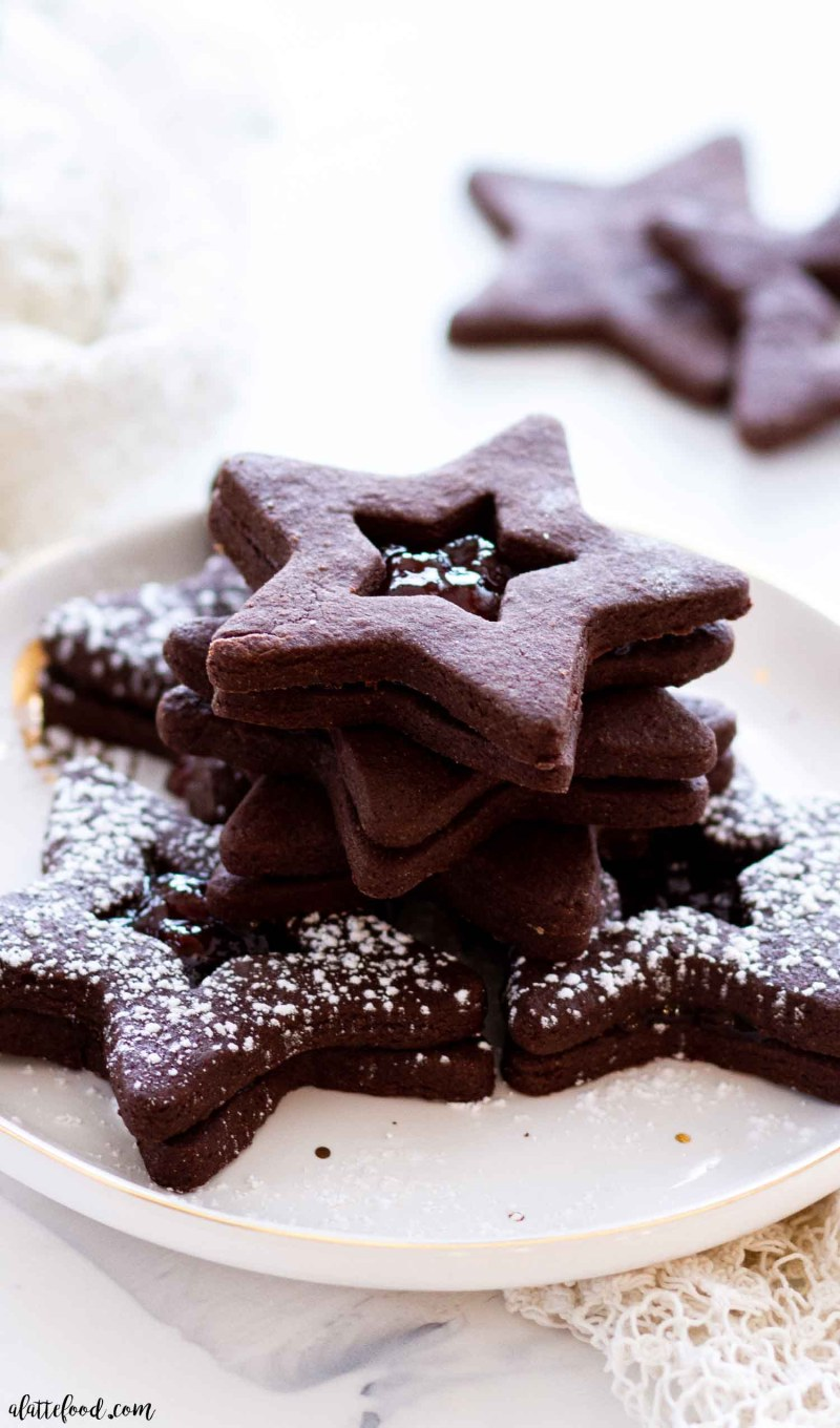 powdered sugar topped chocolate fudge cookies filled with strawberry jam