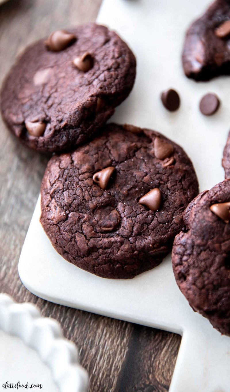 three chocolate fudge cookies with chocolate chips on marble board