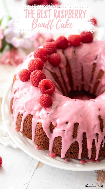 fresh raspberry bundt cake with raspberry glaze on white washed wooden board