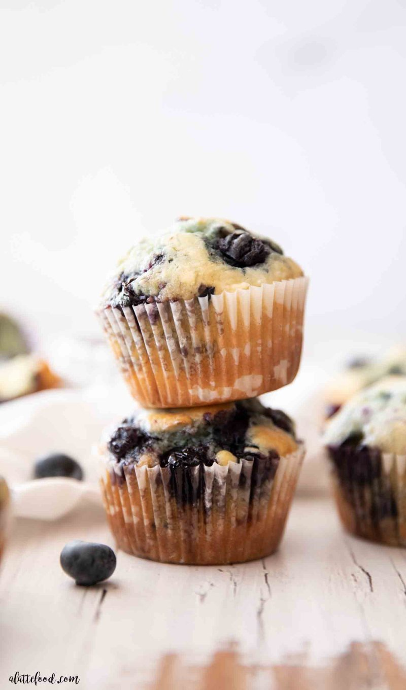 blueberry muffins baked with sour cream stacked on a wooden white board