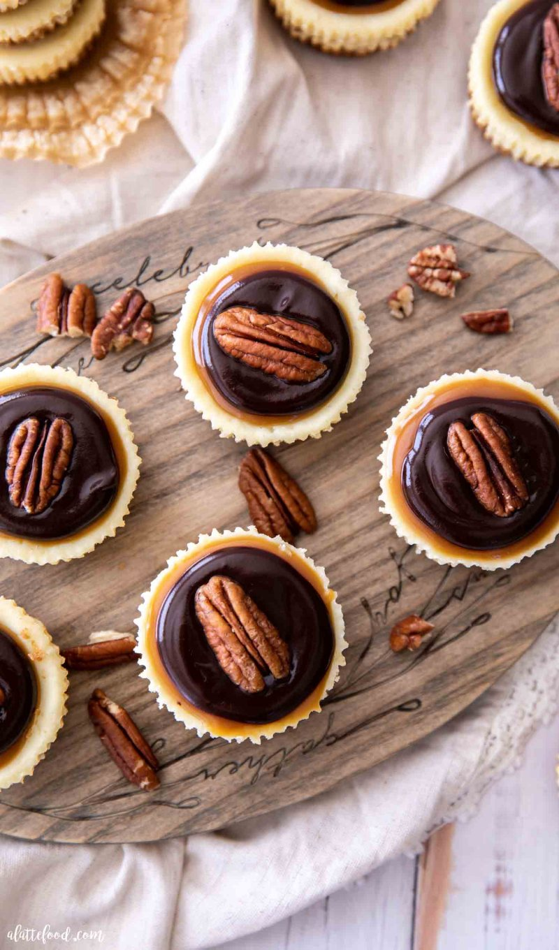 mini turtle cheesecakes with ganache and caramel on a circular wooden cutting board