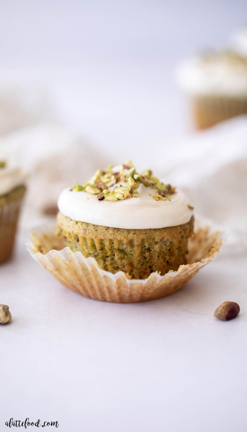 unwrapped pistachio cupcake with honey cream cheese frosting