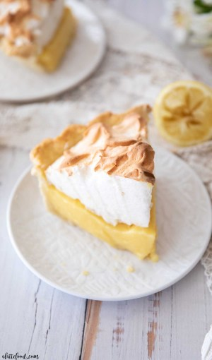 slice of lemon pie with meringue on top on a white circular plate
