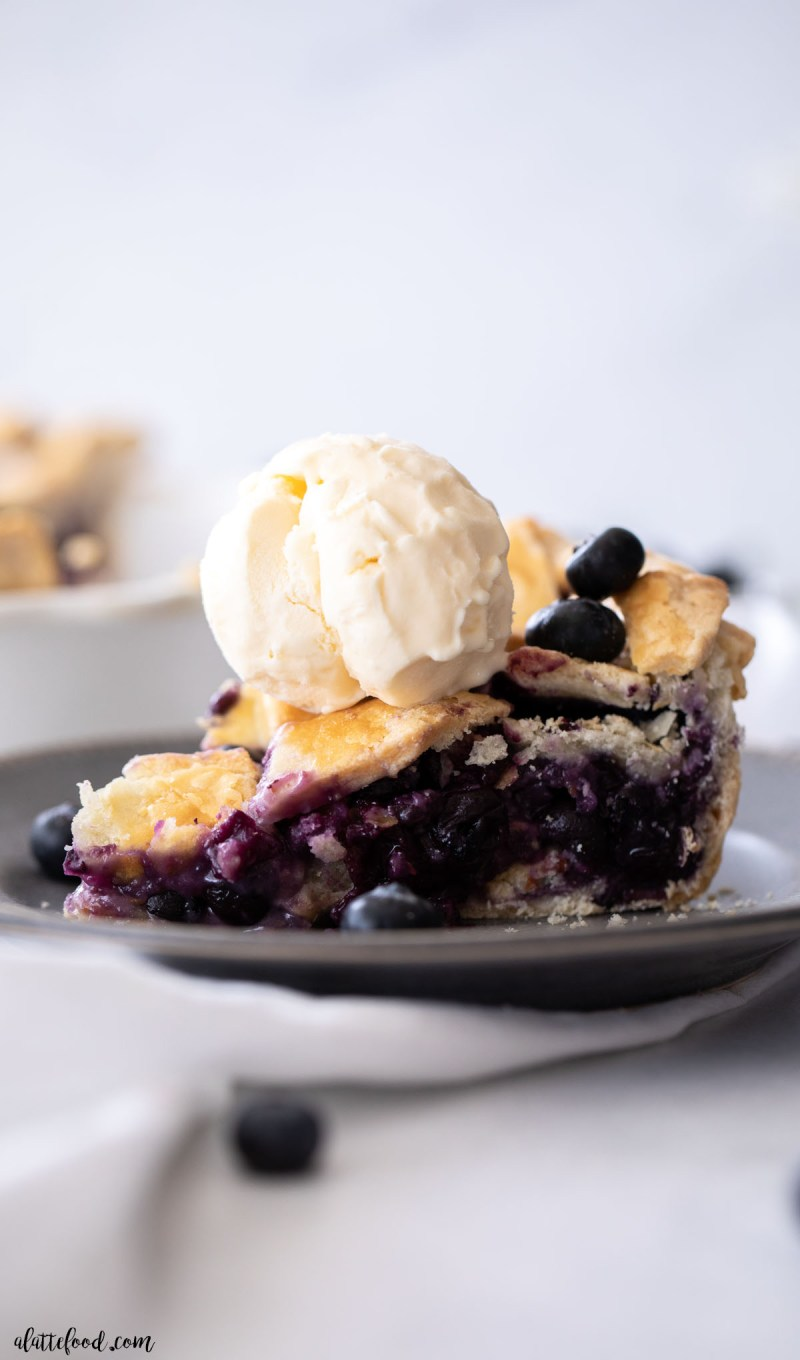 ice cream topped blueberry pie slice on gray plate