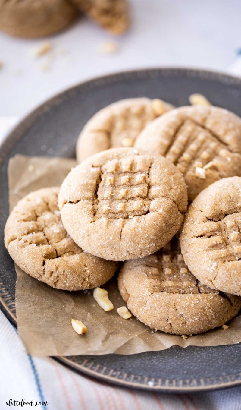 baked peanut butter cookies with peanuts on parchment paper