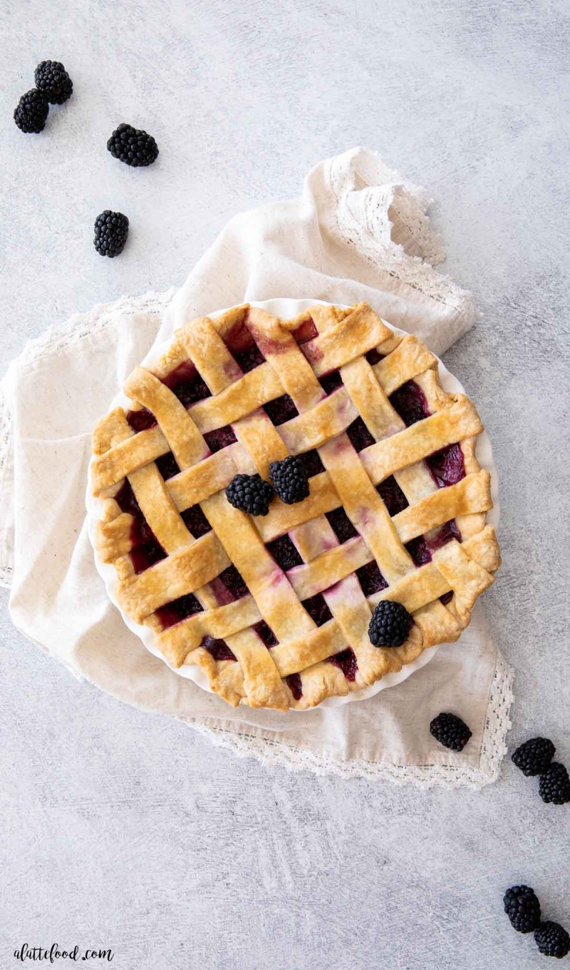 baked blackberry pie with a lattice crust on concrete board