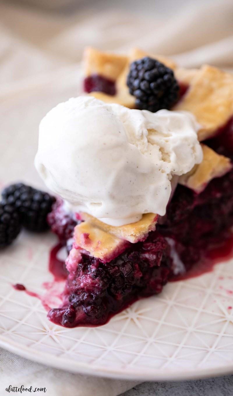 fresh blackberry pie with vanilla ice cream on tan plate
