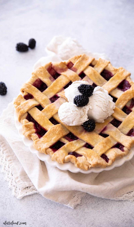 lattice topped blackberry pie with scoops of vanilla ice cream