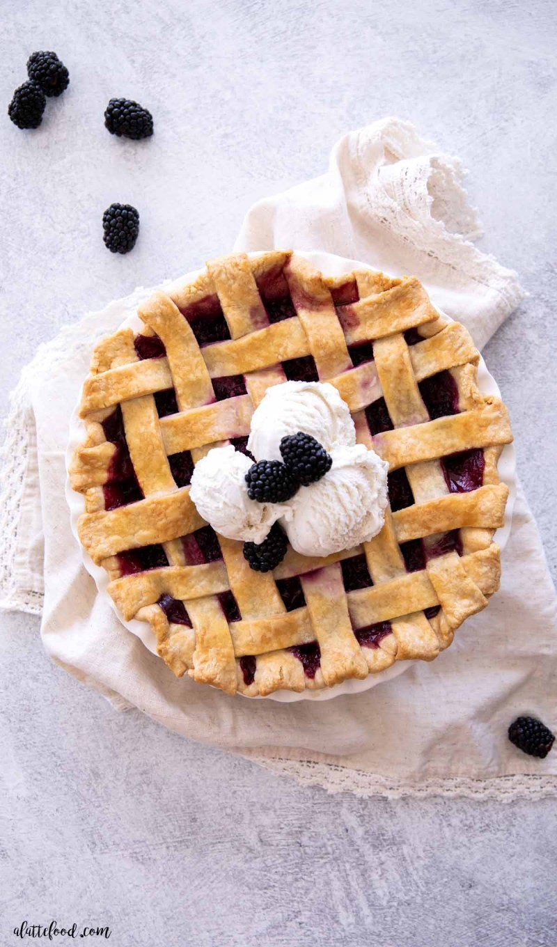 blackberry pie with a lattice crust in a white pie plate with three scoops of ice cream