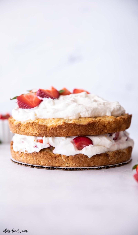 strawberry shortcake cake layered with shortcake biscuits, fresh strawberries and homemade whipped cream