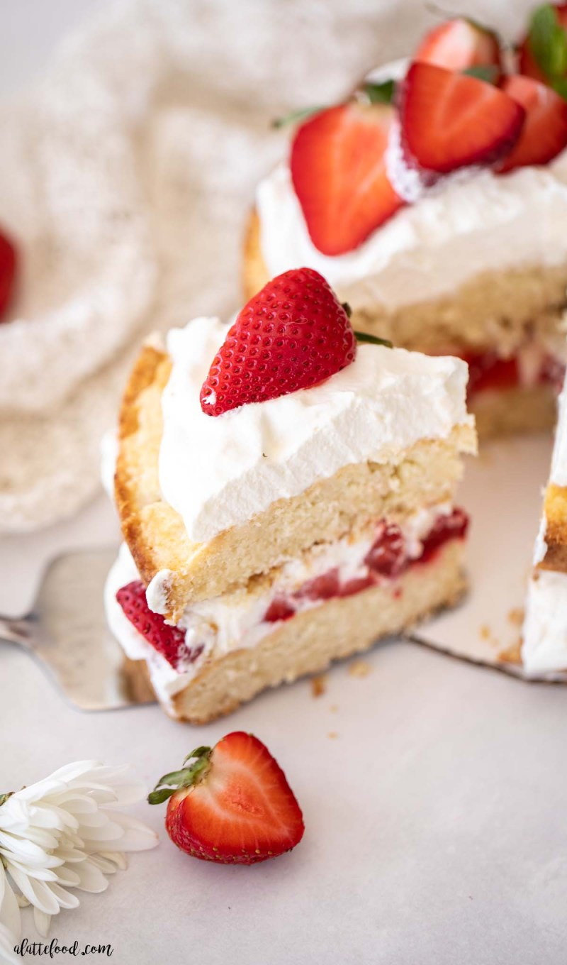 slice of strawberry shortcake layer cake with fresh strawberries and whipped cream