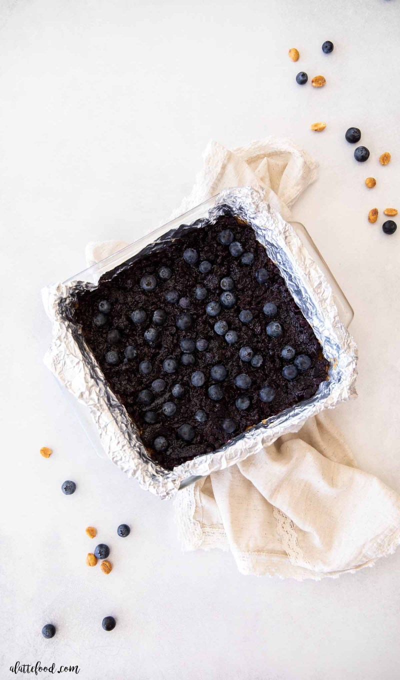 unbaked peanut butter cookie bars with blueberry jam layer on top in a glass dish (step by step)