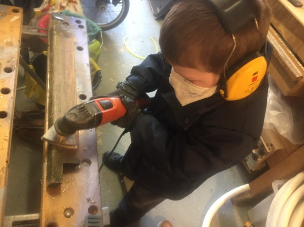 Thomas sanding the hatch trim down with the Fein multitool sporting his PPE 2