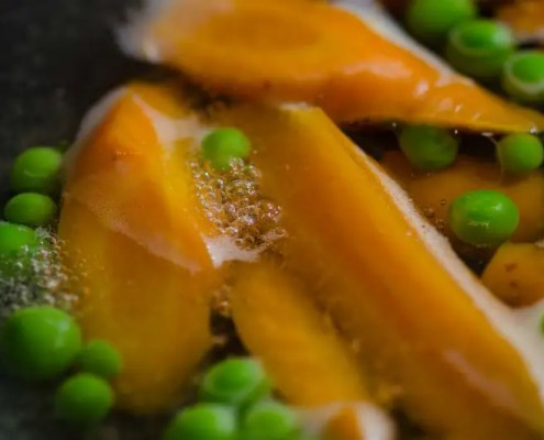 carrots and peas boiling in a pan