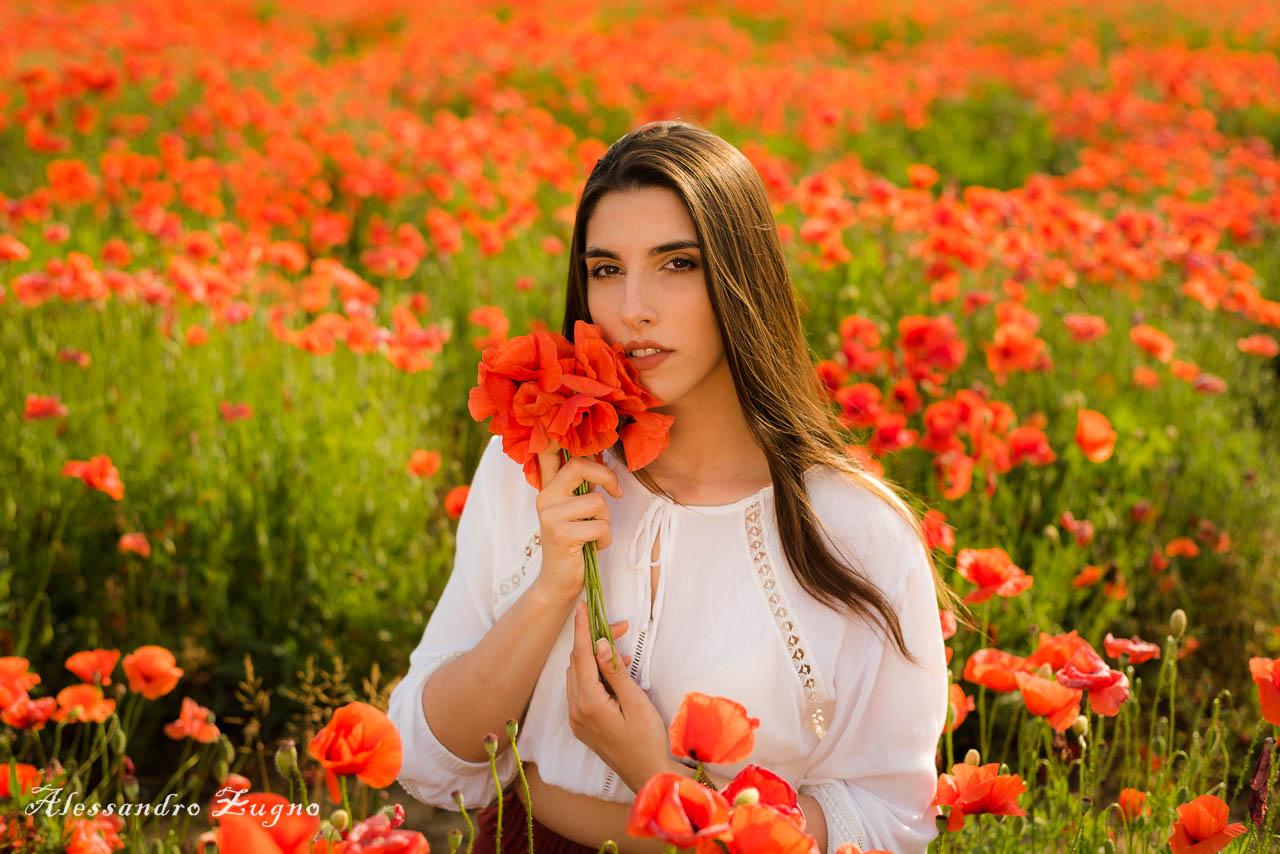 ritratto fotografico di ragazza che posa con mazzo di fiori rossi