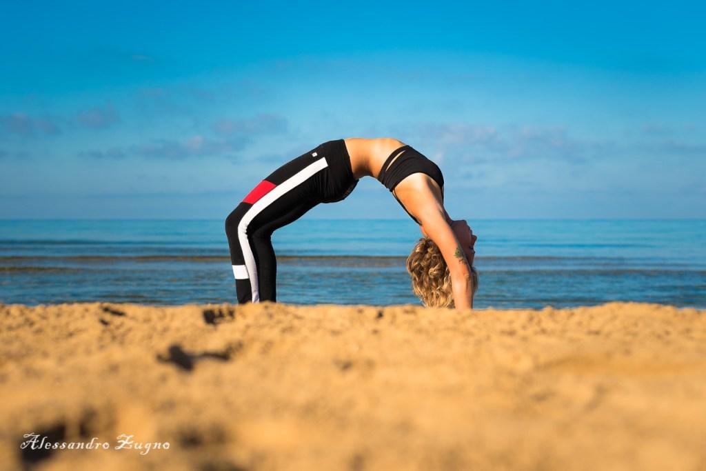 foto di Yoga al mare di ragazza che  pratica posizione del ponte inverso