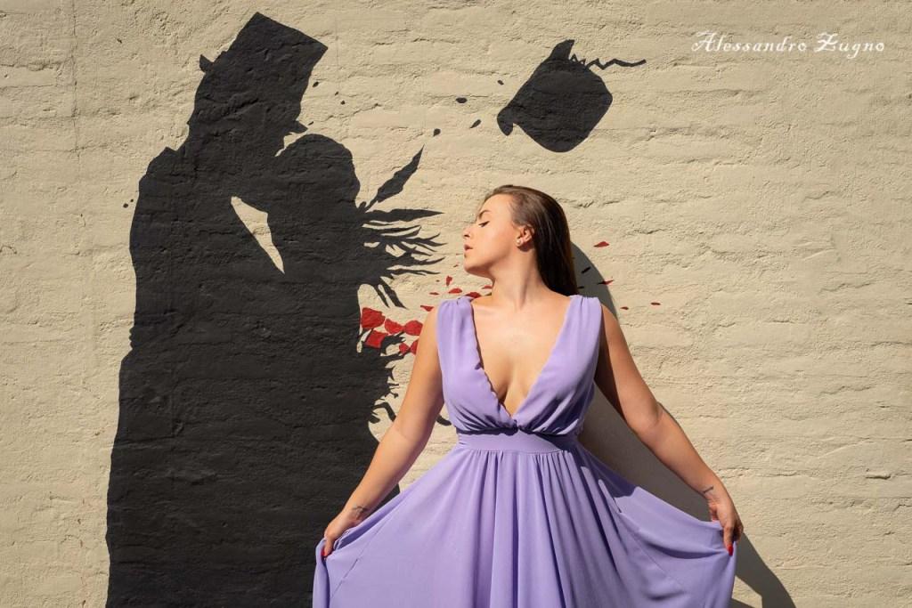 ragazza con vestito elegante mentre posa per foto con murales di kenny random a Padova