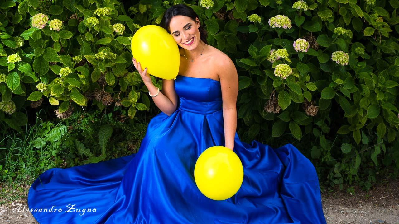 ragazza con vestito blu e makeup fumè che posa per book fotografico all'aperto