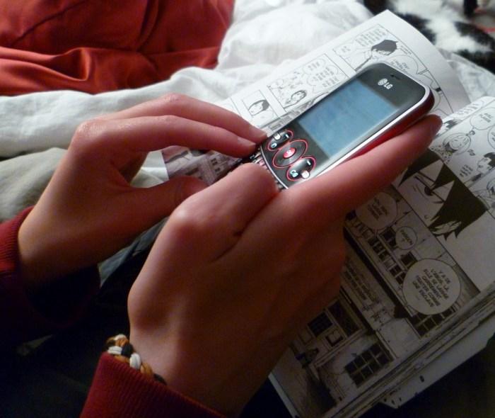 Bild: Olybrius - Junges Mädchen simst beim Lesen eines Mangas. Verwendung unter den Bedingungen CC 3.0 (BY). URL: https://commons.wikimedia.org/wiki/File:Teenage_girl_texting_while_reading_a_manga_1.jpg