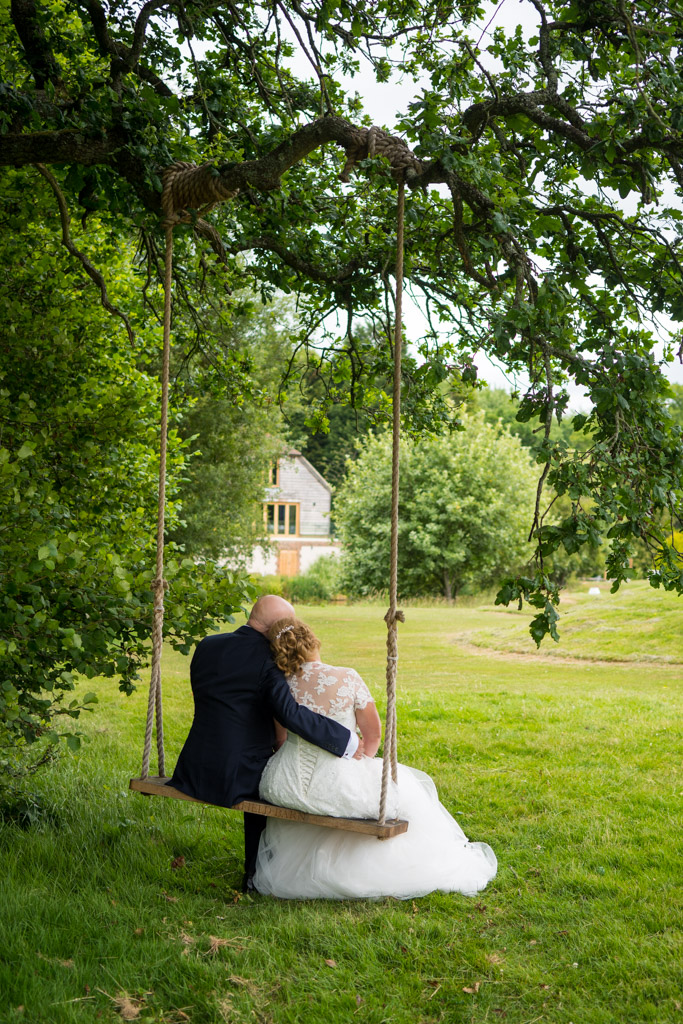 Wedding photo of a couple sitting on a tree swing looking out over a golf green at Brookfield Barn near Horsham
