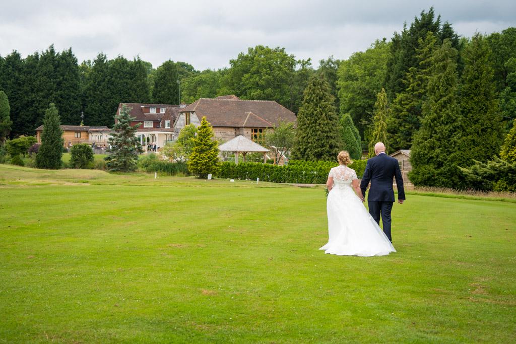 Wedding photo of a couple walking on a golf green at Brookfield Barn near Horsham