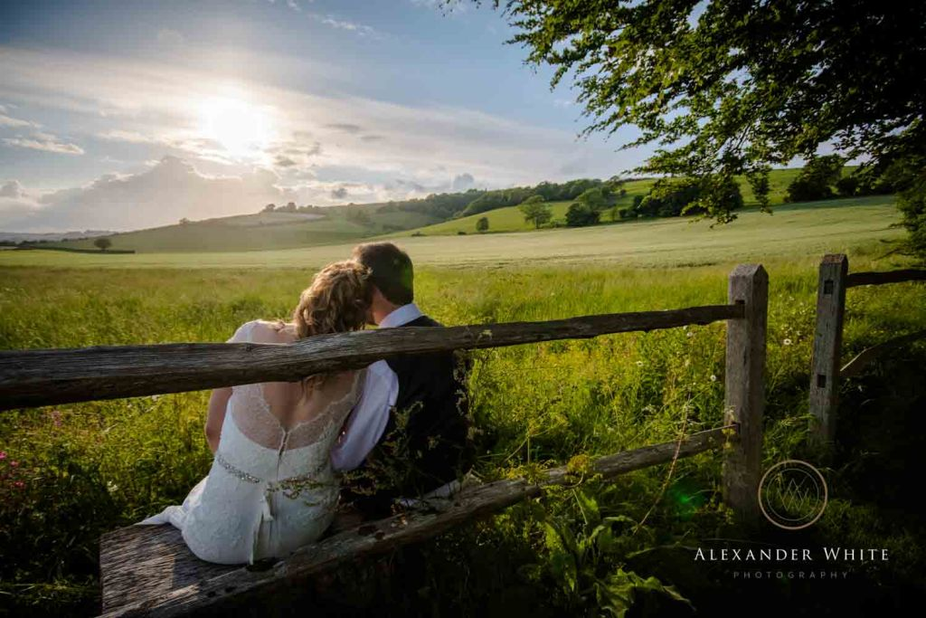 Bride and Groom cuddling up and watching the sunset over East Dean Village in the South Downs