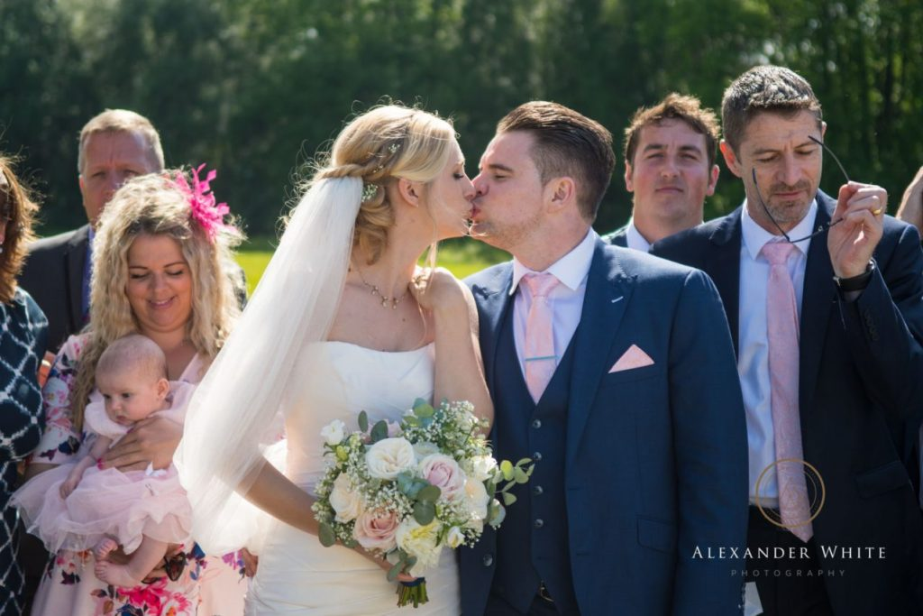 Bride and Groom kiss during a group photo