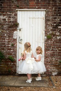 wedding photo of flower girls about to open a door