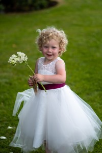 wedding photo of a flower girl holding a flower