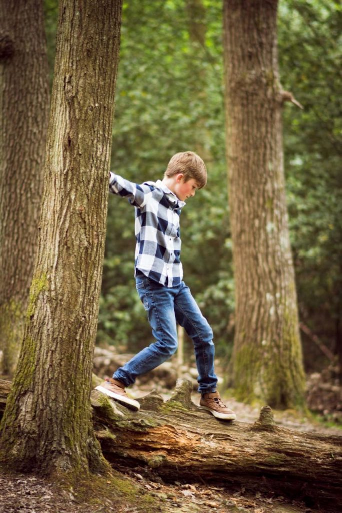 A boy walking along a tree trunk in the woods