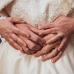 Bride and Groom hands close up with wedding rings visible