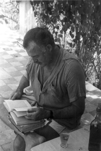 "EH 3963 Ernest Hemingway reading outside at Finca Vigia in Cuba. Please credit ""Ernest Hemingway Collection/John F. Kennedy Presidential Library and Museum, Boston"""