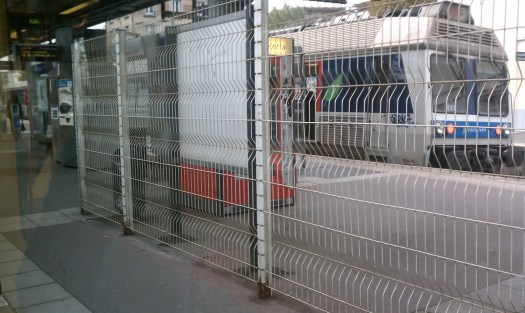 Looking across the T2 platform to a Transilien train at Puteaux. The fence forces passengers to use the faregates to get on a Transilien service. Photo by the author.
