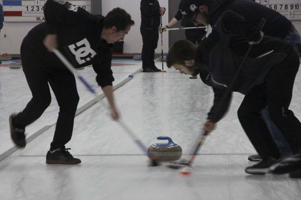 Jamie Caine and a teammate curling at the Garrison Curling Club