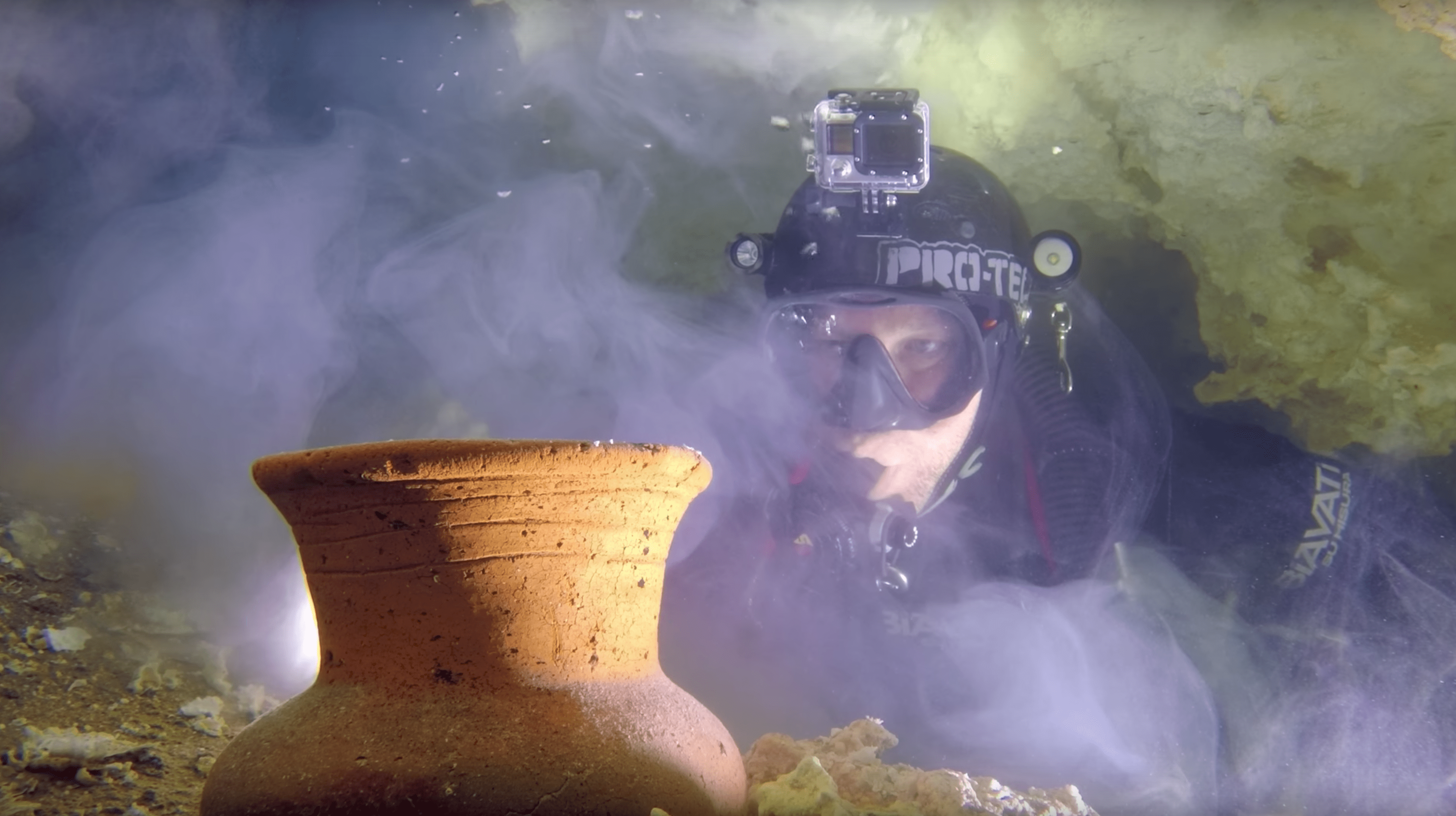 Diver inspects an ancient mayan pot underwater.