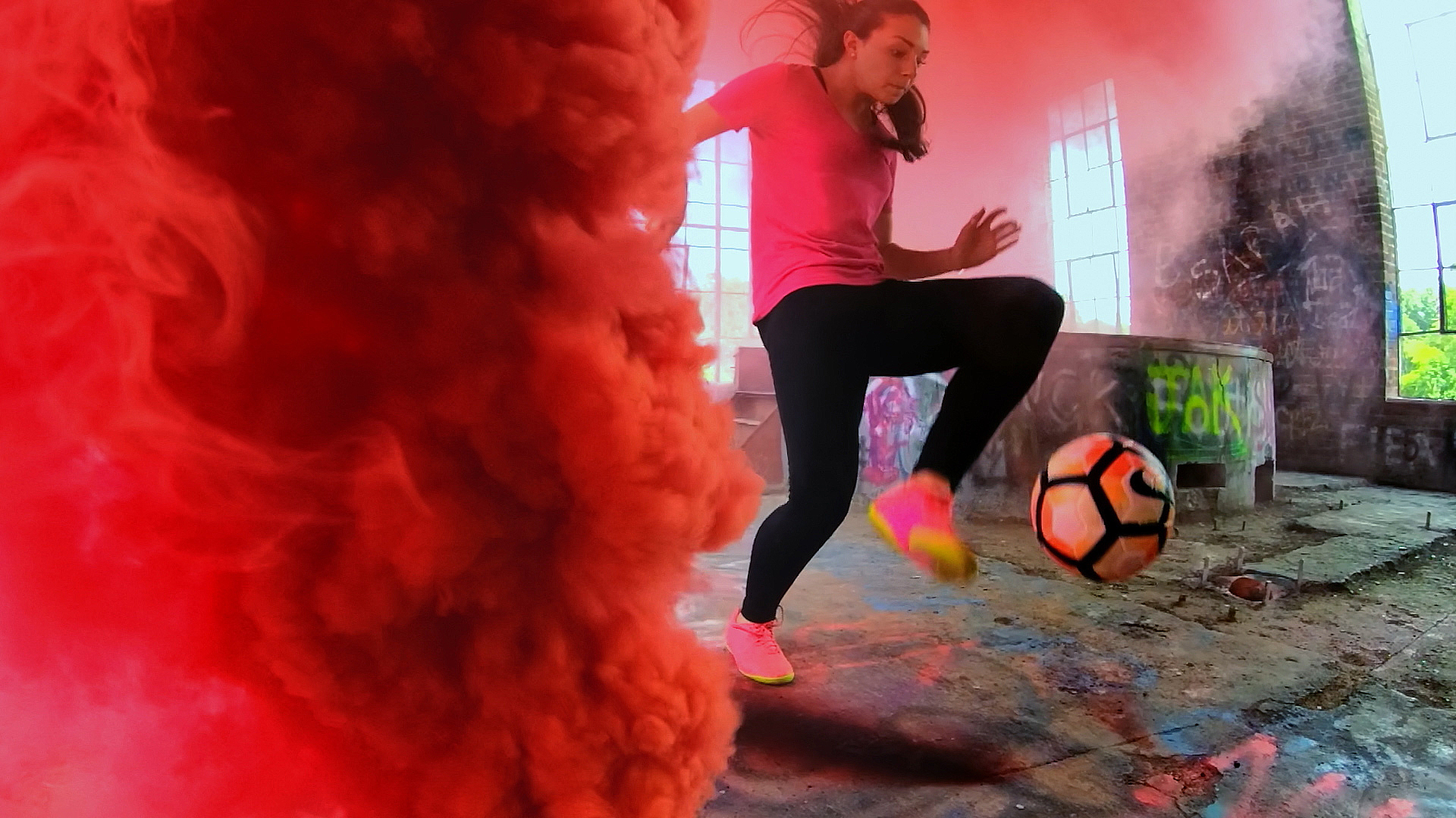 A girl does soccer tricks with colored smoke around her.