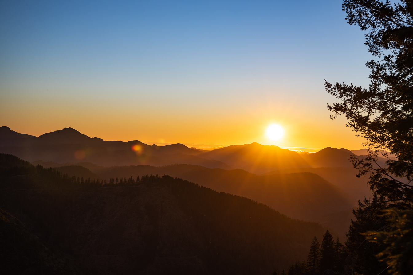 The Sun sets over a Smokey Oregon Wilderness mountain ridgeline.