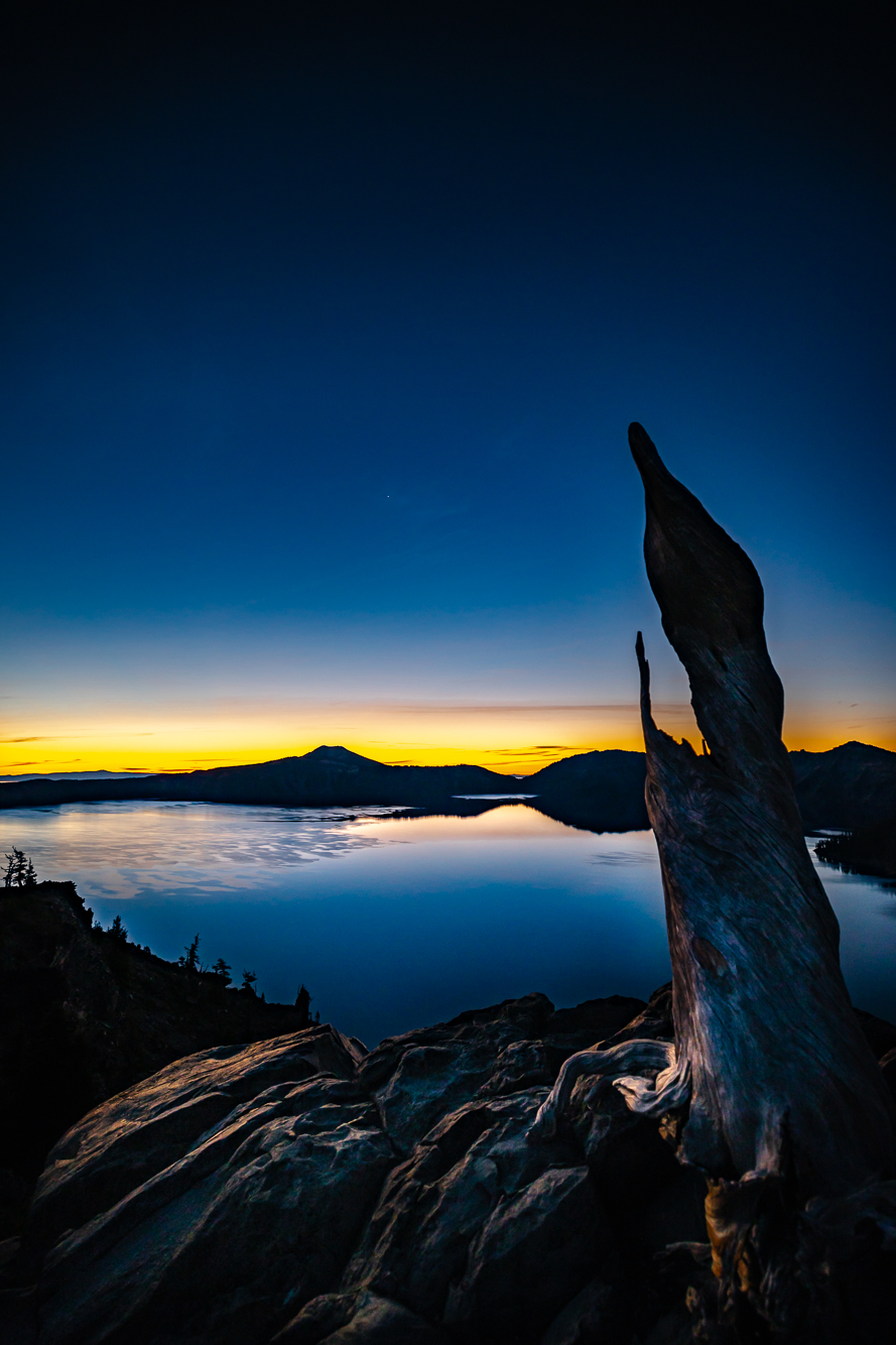 Still water and a glow on the horizon as night shifts to day at Crater Lake National Park.