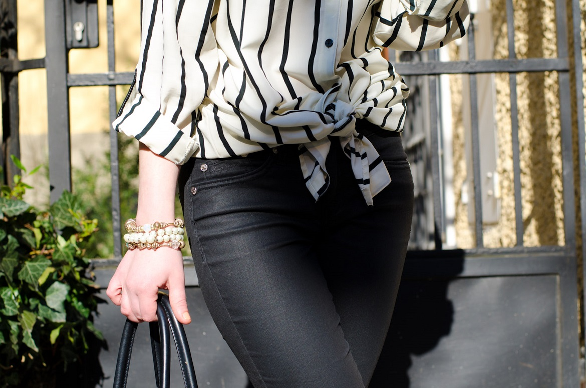 Woman wearing black coated jeans with a white and black striped tie front shirt