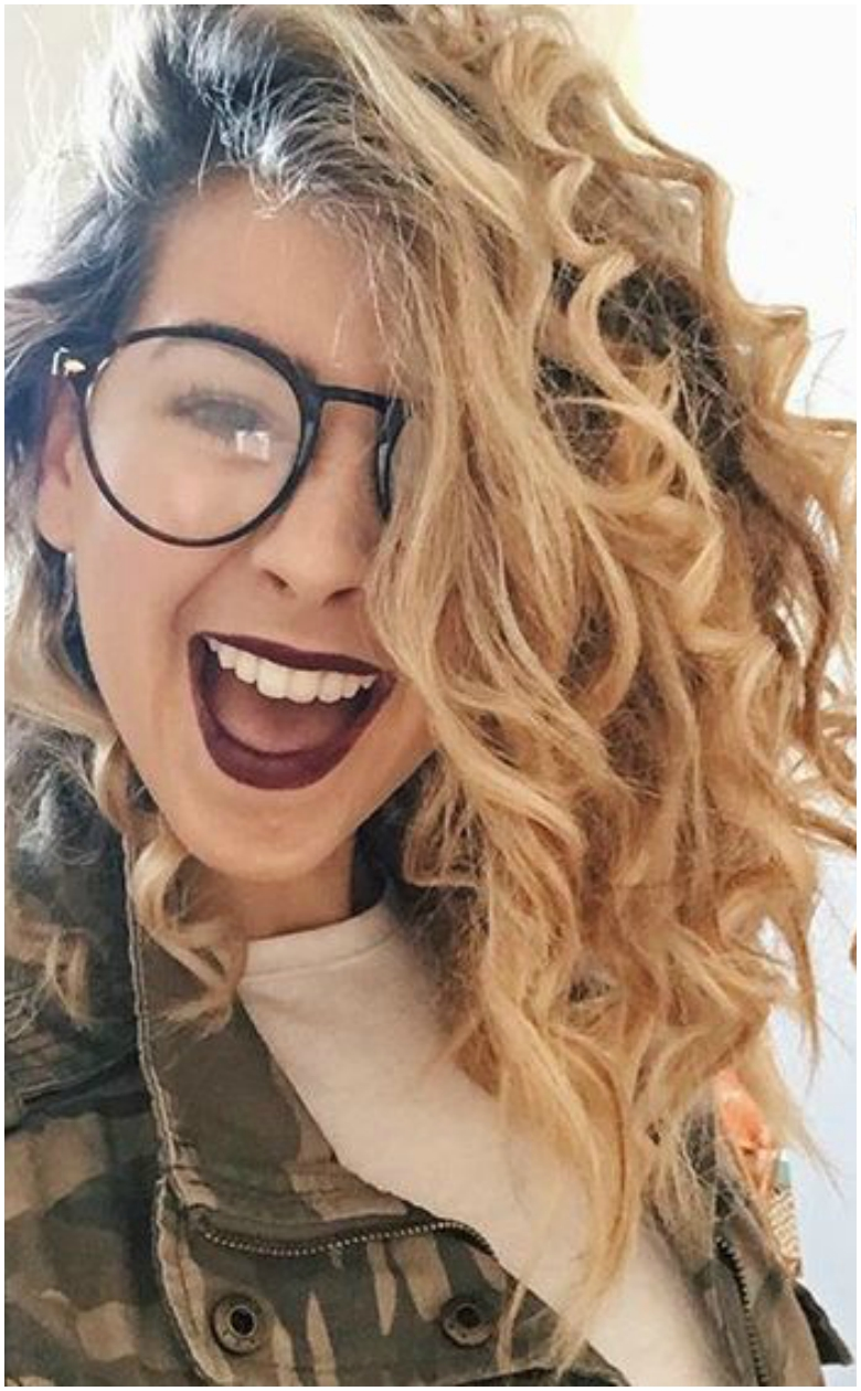 Zoella with corkscrew curls, glasses and camo jacket