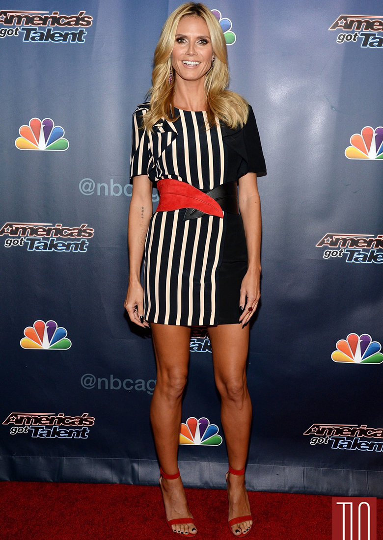 heidi klum wearing black and white dress with red belt and red shoes