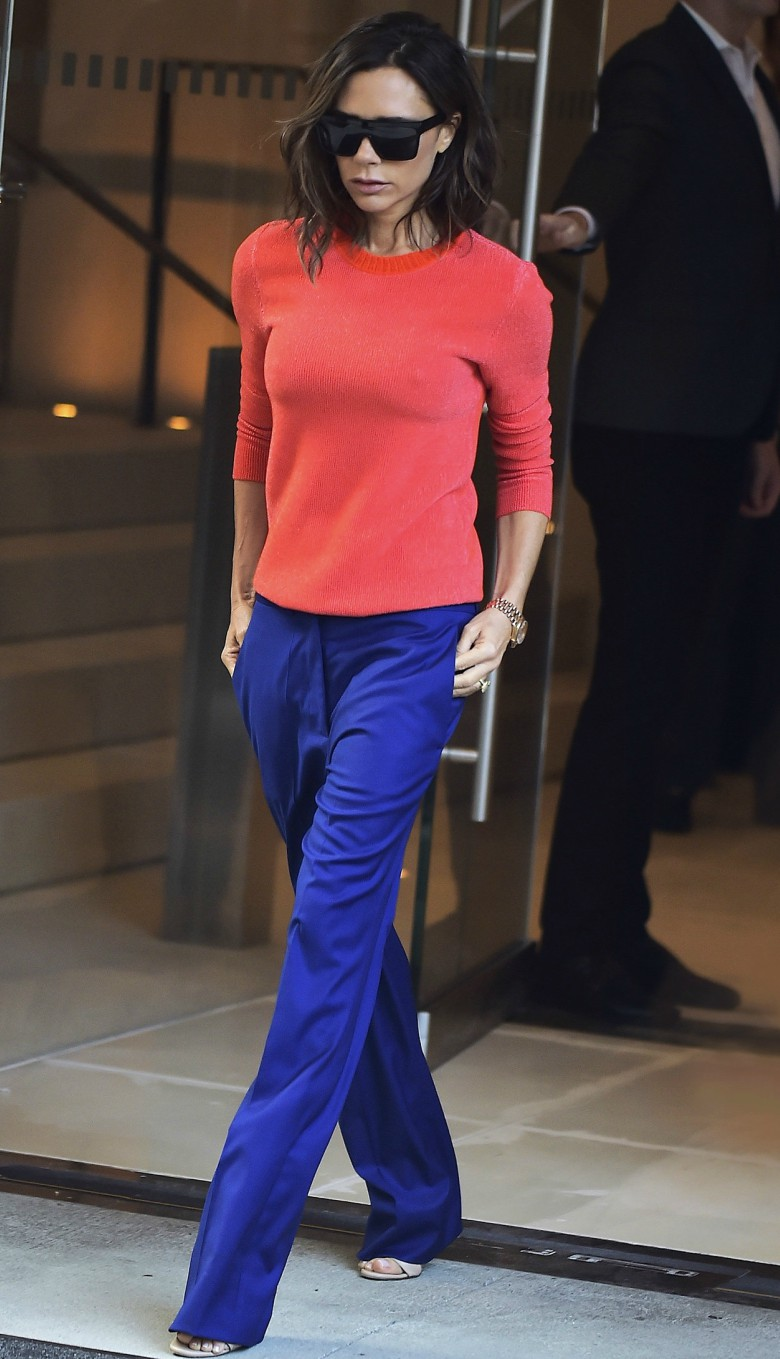 Victoria Beckham street style wearing orange cashmere jumper with blue trousers, sunglasses and heels