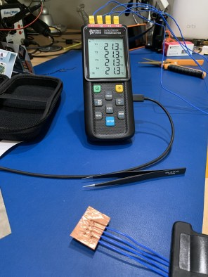 Image showing test setup, with 4 thermocouples sandwiched in the same piece of copper foil tape, and all 4 channels reading 21.3 celsius on the logger screen.
