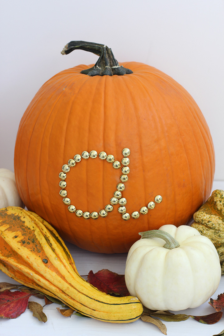 Use gold upholstery tacks to make this simple initial pumpkin this Halloween.