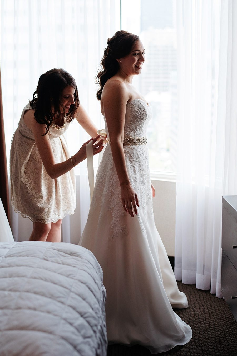 Bride getting help zipping up her dress