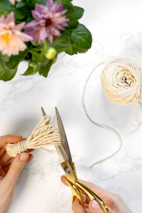 Cutting cotton twine to create handmade tassel for wooden garland decoration