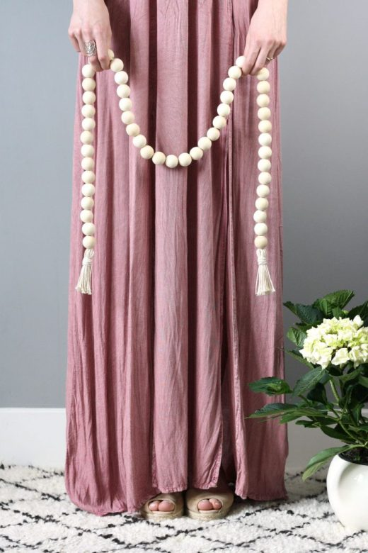 Woman in long flowing pink dress holding DIY wood bead garland