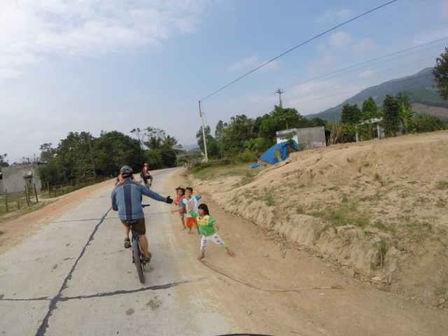 Glenn giving high-fives to the exuberant  children as we rode past.
